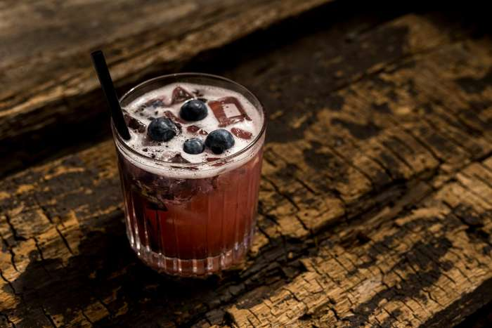 blueberry cocktail on the table of raw pine wood