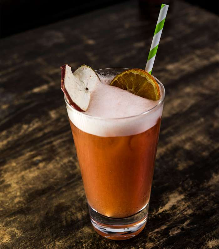 Cocktail with apple and orange presented with a colored straw